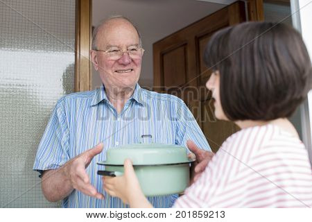 Teenage Girl Bringing Meal For Elderly Male Neighbour