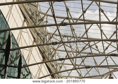 Unrecognizable fragment of modular structural glass ceiling against sky. Glazed aluminum structure with triangular pattern. Abstract architectural background composition.