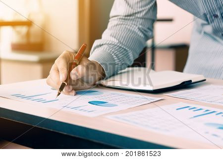 Businessman Pointing Pen On Paperwork Chart Summary Report Graph On Desk For Analyze Data Earnings A