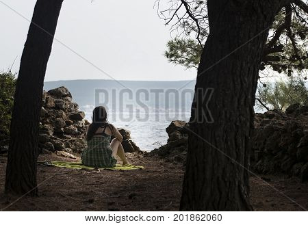 Girl is meditating and resting at sea bellow pinaceae trees.