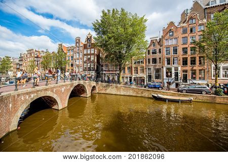 AMSTERDAM, NETHERLANDS - August 07, 2017: View on the water channel with tourists on the street at the red light district during the sunny weather in Amsterdam