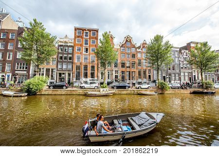 AMSTERDAM, NETHERLANDS - August 07, 2017: View on the water channel with men couple on the boat at the red light district in Amsterdam