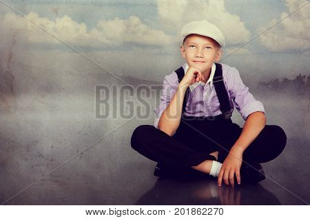 Old fashioned boy sitting and looking up. Closeup. Photo in retro style with old textured paper.