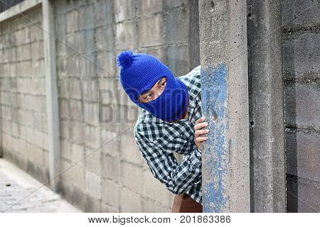 Masked burglar sneaking behind concrete pole before the burglary. Crime concept