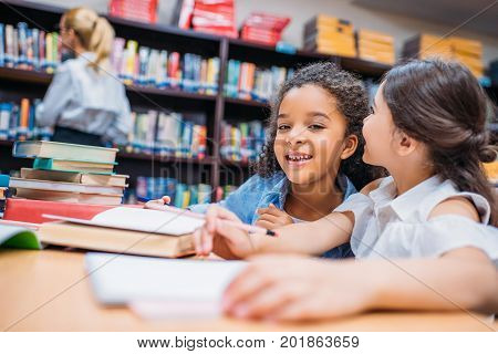two happy little schoolgirls gossiping at library
