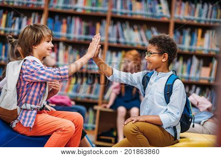 adorable little schoolboys giving high five in library