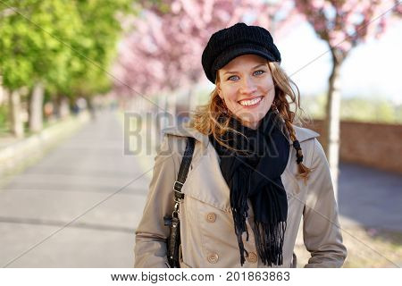 Happy young woman toothy smile at early spring in park