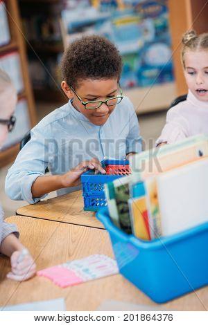 Kids Choosing Supplies In Box