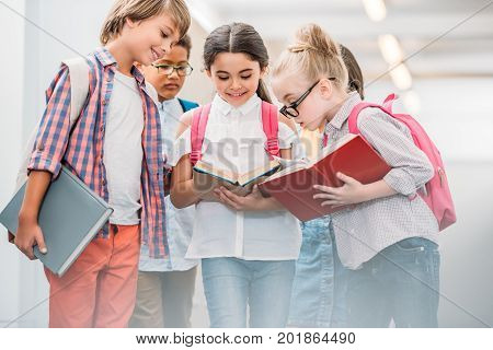 adorable happy scholars looking at book together