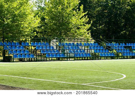 small football field with bleachers on a summer day