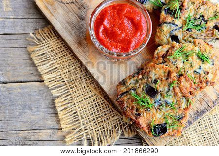 Crispy eggplant burgers with garlic and dill on a wooden board. Tomato sauce in a glass bowl. Vegan eggplant burgers recipe