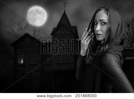 Young woman in black in front of old house on a moonlit night. Halloween concept.