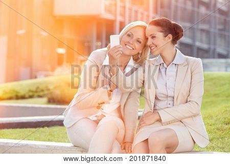 Happy young businesswomen taking self portrait through mobile phone against office building