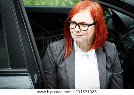 Business Concept Of Success. Serious Successful Woman Boss, In A Suit And Glasses, Rejoices. With A