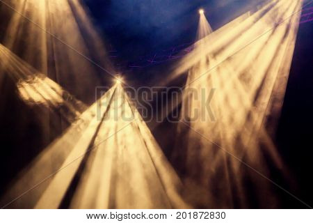 The yellow light rays from the spotlight through the smoke at the theater or concert hall. Lighting equipment for a performance or show.