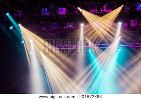 Yellow, white, and blue light rays from the spotlight through the smoke at the theater or concert hall. Lighting equipment for a show or performance.