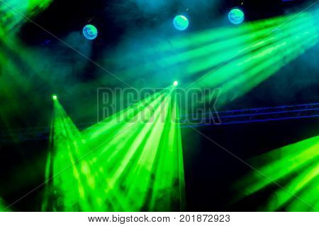 Green light rays from the spotlight through the smoke at the theater or concert hall. Lighting equipment for a performance or show.