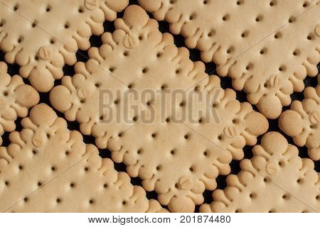 Square biscuit crackers are laid out in rows on a black baking sheet