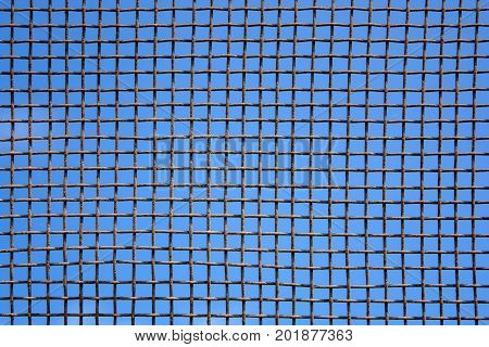Photo of steel mesh wall on blue sky background