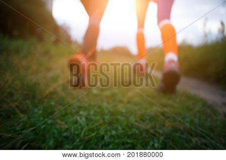 Blurred picture from below of two running girls in forest