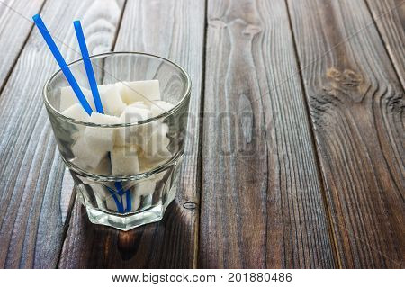 Highball glass with granulated sugar on wooden table. Intake of bad calories. unhealthy diet concept.