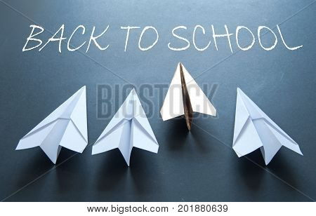 Back to school handwritten on chalkboard with gold paper plane standing out in a line of white plane