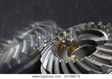 gearbox gears in lubricant-oil against shiny titanium