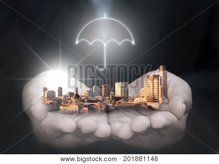 Business man holding company buildings with umbrella protection