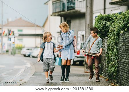 Group of 3 funny schoolkids walking back to school together wearing backpacks holding lunch box and skateboard