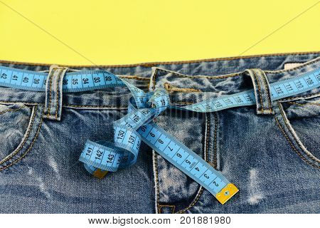 Blue jeans with blue measure tape instead of belt. Top part of denim trousers isolated on yellow background. Healthy lifestyle and dieting concept. Close up of jeans with measure tape around waist.