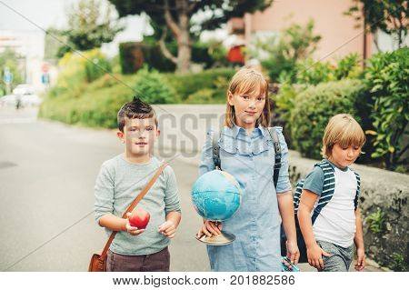 Group of three funny kids wearing backpacks walking back to school. Girl and boys enjoying school activities. Globe lunch box red apple and bag accessories.