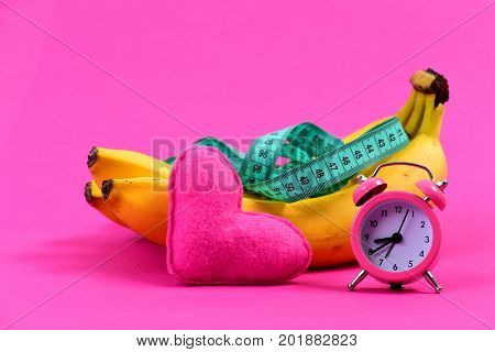 Composition of alarm clock heart and greenish blue measuring tape on bananas isolated on raspberry pink background