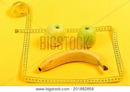 Square made of tape for measuring in yellow color and sad face made of banana and apples inside isolated on bright yellow background. Concept of emotions and fruit diet