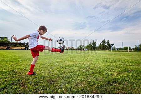 Boy Playing With Football Ball On Playing Field.