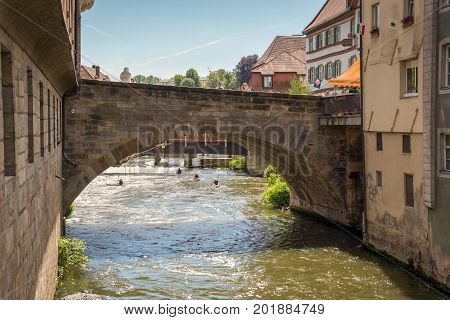 Bamberg Germany - May 22 2016: Old bridge over the Regnitz river in downtown of Bamberg Upper Franconia Bavaria Germany. Bamberg is under UNESCO protection.
