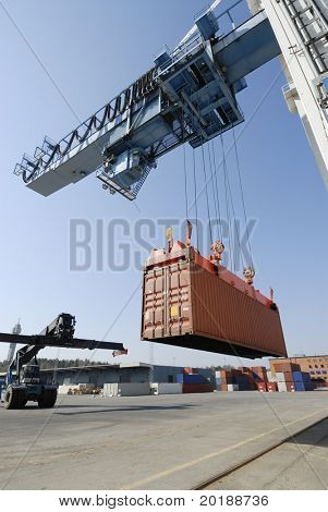 crane lowering container to waiting forklift truck