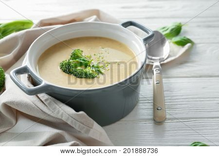 Broccoli cheddar soup in casserole on wooden kitchen table