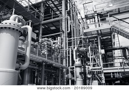 refinery interior with miles of pipelines, pumps and tubes, silver-blue toning