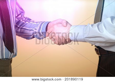 Closeup midsection of two businessmen shaking hands against colored background