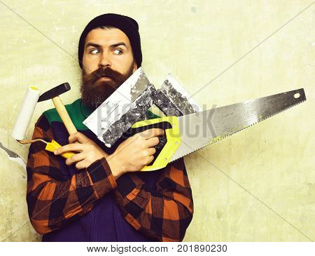 Bearded Man Holding Various Building Tools With Surprised Face