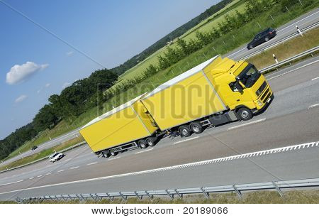 large yellow truck speeding on freeway, fields and forrest in background
