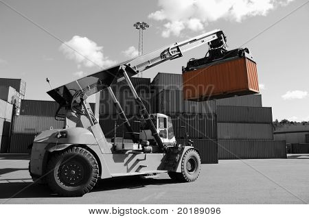 forklift stacking containers in port, dual color concept in black/white and orange