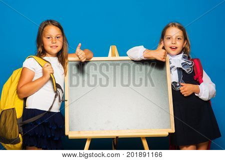 Children Hold Big Schoolbags, Copy Space. Schoolgirls With Smiling Faces