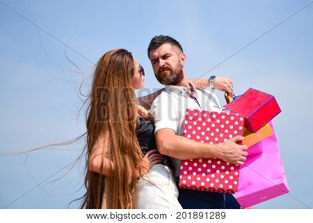 Couple carries pink packets and box on sky background. Shopping and love concept. Sexy girl and guy with serene faces make purchases. Man with beard and long haired woman hold shopping bags
