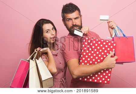Man With Doubtful Face And Lady Hold Credit Cards