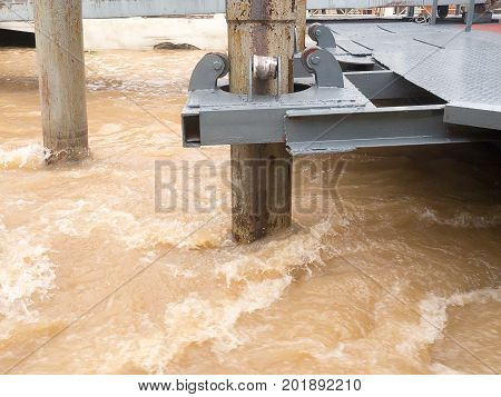 Rust roller support pole of pontoon in rapid stream flowing river.