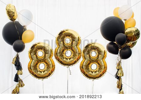 Decoration for anniversary, celebration of the eight hundred and eighty-eight anniversary, white background, gold and black balloons with tassels