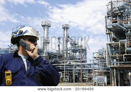 engineer talking in mobile-phone in front of large oil refinery, massive pipelines constructions