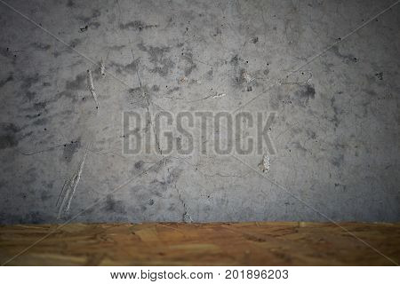 Decorative grey concrete wall and wooden table top, vignetted background. Selective focus on wall