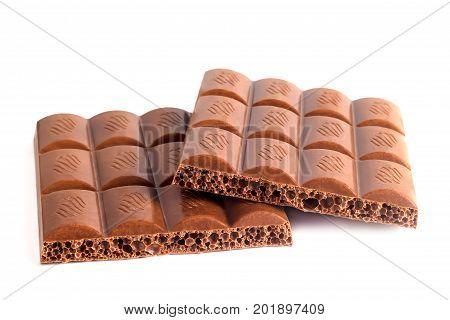 Tile of porous chocolate broken on papolus on white background
